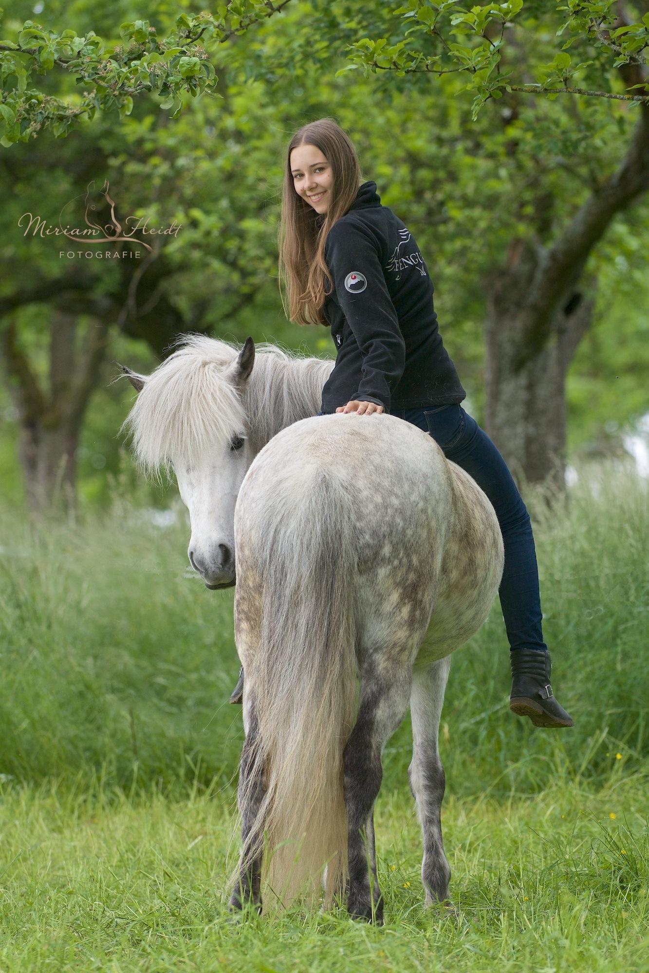 Mädchen sitzt ohne Sattel und Zaum auf ihrem Pony